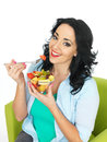 Happy healthy young fit woman eating a bowl of fresh exotic fruit salad with dark wavy hair with hispanic features holding and Royalty Free Stock Photo