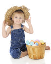 Happy with her ragged hat an adorable preschool farm girl happily sitting in straw a fruit basket full of easter eggs beside on a Royalty Free Stock Image