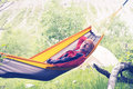 Happy hiker is relaxing in hammock on the alpine meadow Royalty Free Stock Photo