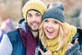 Happy hipster couple in love take a selfie photo during sunny day in autumn. Best friends with winter clothes sharing free time. Royalty Free Stock Photo