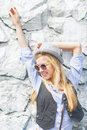 Happy hipster girl posing against rocky wall outdoors in hat Royalty Free Stock Image