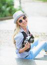 Happy hipster girl sitting on stairs with retro photo camera in hat Stock Photography