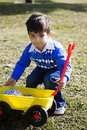 Happy hispanic boy playing with his toy truck Royalty Free Stock Image