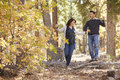 Happy Hispanic couple hold hands hiking together in forest