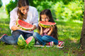 Happy hispanic family eating watermelon at park Royalty Free Stock Image