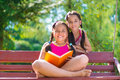 Happy hispanic sisters in summer park reading book Royalty Free Stock Photography