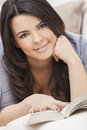 Happy Hispanic Woman Reading Paperback Book Stock Image