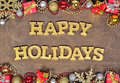 Happy holidays golden text and Christmas decorations Royalty Free Stock Photo