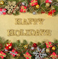 Happy holidays golden text and spruce branch and Christmas decor Royalty Free Stock Photo