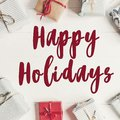 Happy holidays text, seasonal greetings card sign. wrapped prese Royalty Free Stock Photo