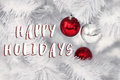 happy holidays text sign on red and silver ornament balls on white christmas tree branches. space for text. greeting card. winter