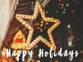 Happy Holidays  text sign on stylish christmas golden star illumination and fir branches with red and gold baubles, golden lights Royalty Free Stock Photo