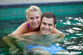 Happy honeymoon in a swimming pool smiling young couple relaxing tropical resort Royalty Free Stock Photo