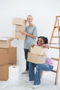 Happy housemates carrying cardboard moving boxes in their new home Royalty Free Stock Photography
