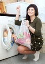 Happy housewife loading the washing machine with laundry bag Stock Photography