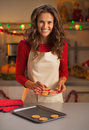 Happy housewife putting christmas cookies from pan to plate Royalty Free Stock Photo