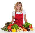 Happy housewife with red apron and fresh vegetables Royalty Free Stock Photo