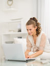 Happy housewife sitting on divan and using laptop young Royalty Free Stock Photos