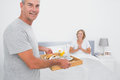 Happy husband bringing breakfast in bed to delighted wife looking at camera bedroom at home Stock Image