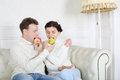 Happy husband and wife bite fruit and sit on white sofa in room at home Stock Photos