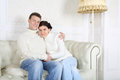 Happy husband and wife hug and look at camera on white sofa home Royalty Free Stock Image