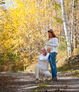 Happy husband and wife prospective parents married couple hugs his pregnant at walk in autumn forest Stock Photography