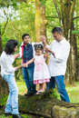 Happy indian family outdoor fun at candid portrait of parents and children having at garden park exploring nature leisure Stock Images