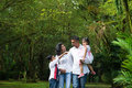 Happy indian family outdoor weekend at parents and children walking on garden path exploring nature leisure lifestyle Stock Photography