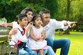 Happy indian family at outside outdoor park candid portrait of parents and children having fun garden park fingers pointing away Stock Image