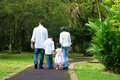 Happy indian family walking outdoor at rear view of parents and children on garden path exploring nature leisure lifestyle Stock Photo