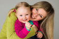 Happy infant child girl with mother on gray Stock Image