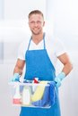 Happy janitor with a tub of cleaning supplies or cleaner wearing an apron and gloves carrying as he goes about his work at the Stock Photography
