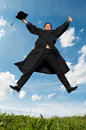 Happy jumping graduate outdoors Royalty Free Stock Photos
