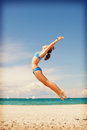 Happy jumping woman on the beach bright picture of Royalty Free Stock Photo