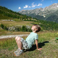 A happy kid is basking in sunlights on mountain slope Royalty Free Stock Photography