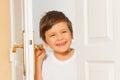 Happy kid boy looking through the doorway Royalty Free Stock Photo