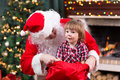Happy kid boy pulls gift out Santa Claus sack Royalty Free Stock Photo