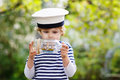 Happy kid boy in skipper uniform playing with toy ship against green tree summer background Stock Photography