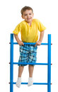 Happy kid boy on top of gymnastics ladder making exercises Royalty Free Stock Image