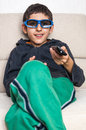 Happy kid d polarized glasses with remote control looking at movie home cinema using Royalty Free Stock Photos