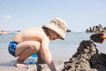 Happy kid digging a hole in the beach in the sand and builiding a castle Royalty Free Stock Photo