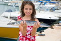 Happy kid fisherwoman with barracuda fish catch in mediterranean marina Royalty Free Stock Image