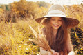 Happy kid girl in straw having fun outdoor on summer sunny field Royalty Free Stock Photo