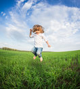 Happy kid jumping in green field against blue sky summer vacation concept Royalty Free Stock Photography