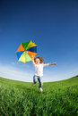 Happy kid jumping in green field against blue sky summer vacation concept Royalty Free Stock Images