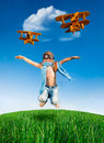 Happy kid jumping outdoors dressed as a pilot in green field against blue sky summer vacation concept Royalty Free Stock Photos