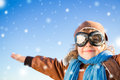 Happy kid playing in the role of pilot against blue winter sky background Royalty Free Stock Photography