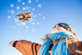 Happy kid playing with toy airplane against blue winter sky background Stock Images