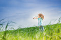 Happy kid with raised arms in green spring field against blue sky freedom and happiness concept Stock Photos