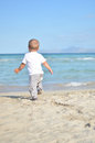 The happy kid is running to the sea a baby Royalty Free Stock Photo